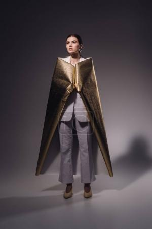 stylish woman in white suit covered in golden wrapping paper posing on dark background