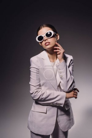 portrait of stylish woman in white suit and eyeglasses posing on dark backdrop
