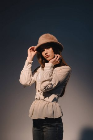 portrait of beautiful young woman in stylish clothing and hat posing on dark background