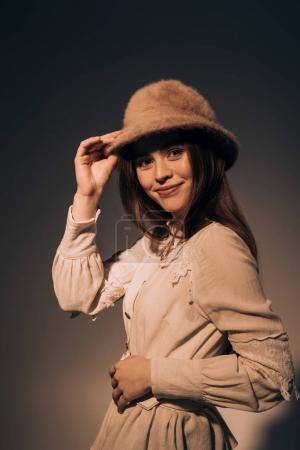 Foto de Retrato de hermosa mujer sonriente con sombrero elegante mirando a cámara - Imagen libre de derechos