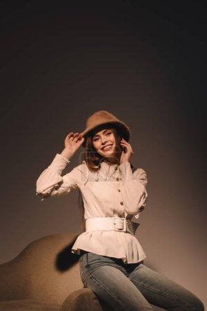 Photo pour Portrait de la belle femme souriante au chapeau élégant assis sur le fauteuil et regarder la caméra - image libre de droit