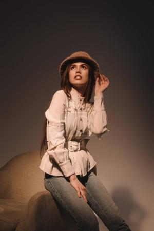 Foto de Retrato de mujer atractiva pensativa en moda sombrero sentado en sillón sobre fondo oscuro - Imagen libre de derechos