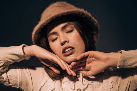 Photo for Portrait of beautiful young woman in stylish hat with eyes closed isolated on black - Royalty Free Image