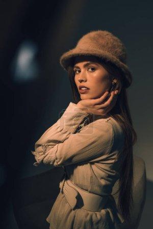 Photo pour Vue latérale d'une belle jeune femme au chapeau élégant regardant la caméra - image libre de droit