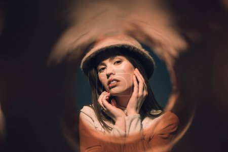 portrait of fashionable woman in hat looking at camera