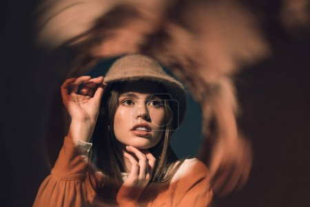 portrait of pensive woman in stylish hat looking away