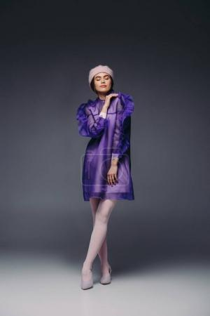 fashionable woman in purple dress and hat with eyes closed posing on black background