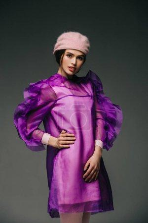 Photo pour Portrait d'une femme élégante en robe violette et chapeau posant sur fond noir - image libre de droit