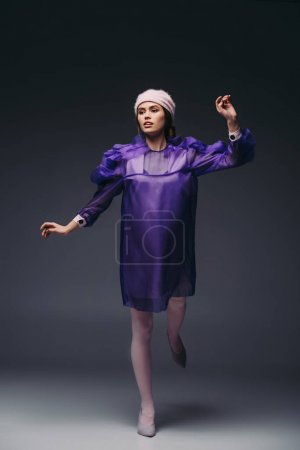 attractive woman in purple dress and hat posing on black background