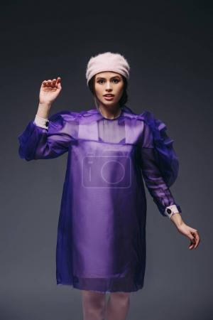 portrait of stylish woman in purple dress and hat posing on black background