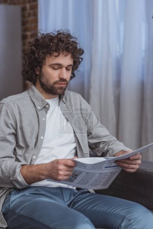 handsome man reading business newspaper in living room