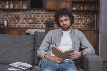 Photo pour Beau livre de lecture homme sur canapé à la maison - image libre de droit