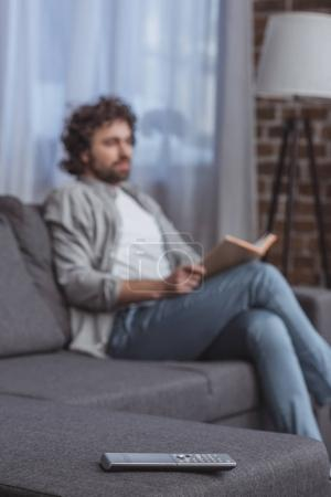 handsome man holding book with remote control on foreground