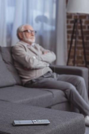 handsome grey hair man sitting on sofa with crossed arms with remote control on foreground