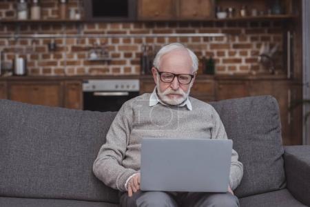homme Senior à l'aide d'ordinateur portable