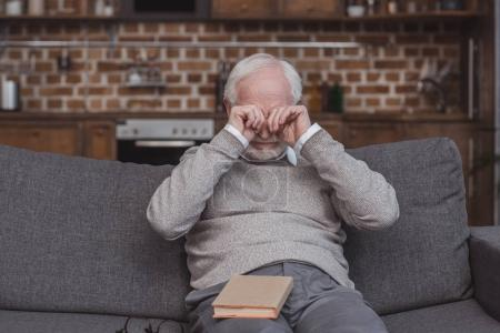handsome grey hair man rubbing eyes at home