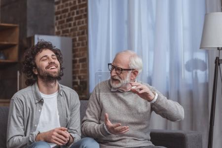 Photo pour Un fils adulte et senior père parler et rire à la maison - image libre de droit