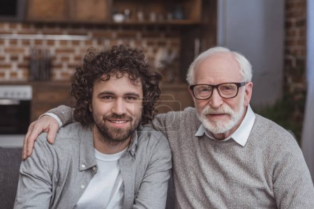 portrait of adult son and senior father hugging at home