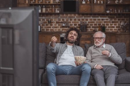 Photo pour Un fils adulte et senior père regarder la télévision sur le canapé à la maison - image libre de droit