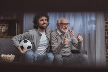 happy adult son hugging senior father while showing thumbs up at home