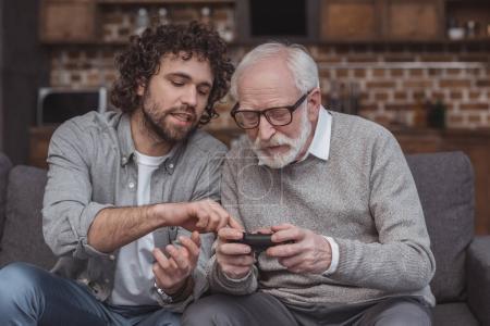 adult son describing senior father joystick at home