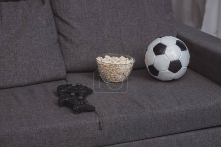 bowl with popcorn, football ball and gamepads on sofa
