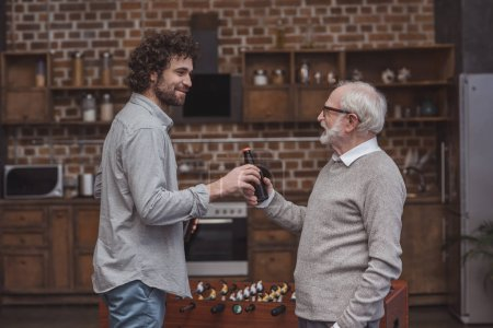 Photo for Adult son giving senior father bottle of beer at home - Royalty Free Image