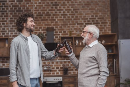 Photo for Happy adult son and senior father clinking with bottles of beer at home - Royalty Free Image