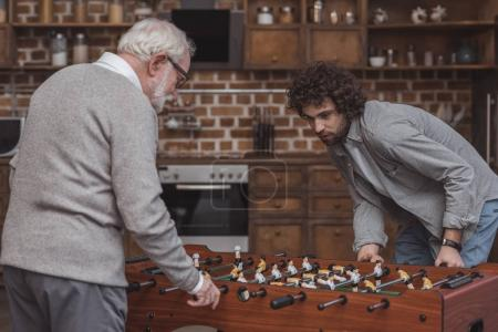 adult son and senior father playing table soccer at home