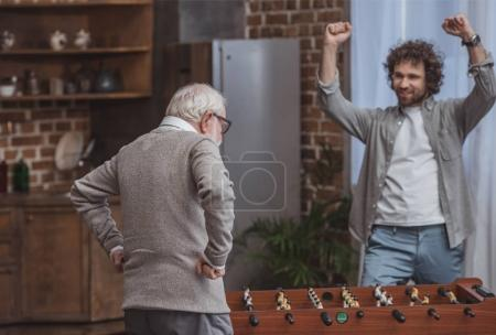 adult son showing yes sign after winning senior father in foosball at home