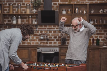 happy senior father showing yes sign after winning adult son in foosball at home