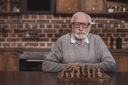 handsome grey hair man sitting at table with chessboard and looking at camera