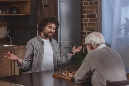 adult son gesturing while playing chess with senior father at home