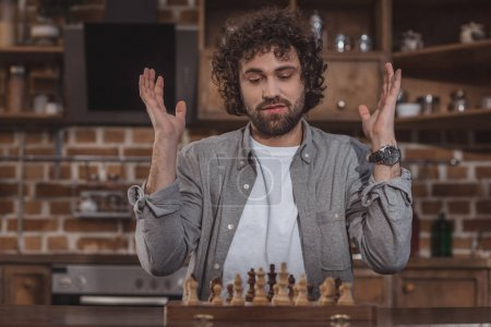 handsome man gesturing and looking at chess at home