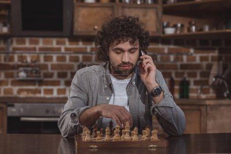 Photo pour Bel homme parler de smartphone et de jouer aux échecs à la maison - image libre de droit
