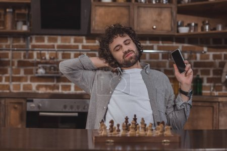 tired handsome man holding smartphone and stretching on chair at home