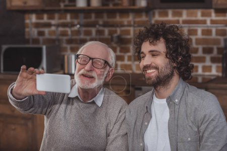 smiling adult son and senior father taking selfie in kitchen