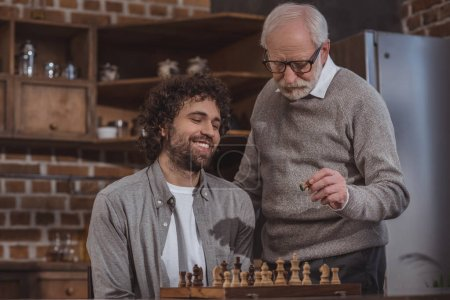 smiling adult son and senior father playing chess at home