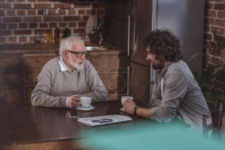 adult son and senior father talking at drinking coffee in kitchen