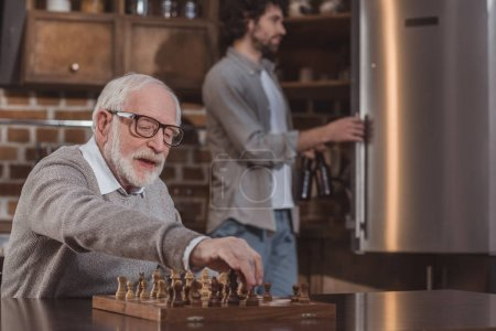 Photo for Adult son looking in fridge and senior father playing chess at home - Royalty Free Image