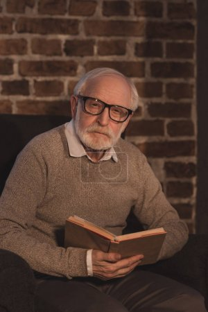 handsome grey hair man holding book and looking at camera at home