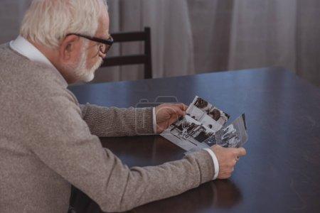 side view of grey hair man sitting at table and looking at photos at home