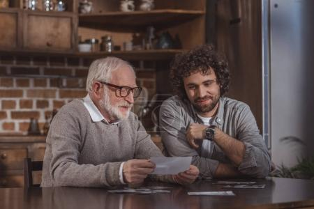 Photo for Adult son and senior father looking at old photos at home - Royalty Free Image