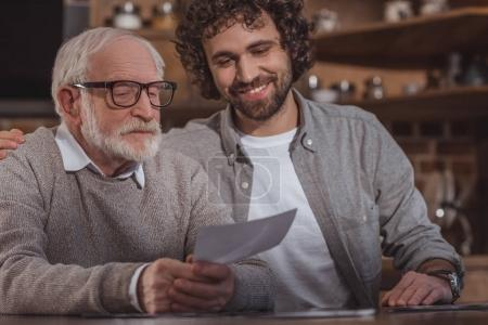 smiling adult son hugging senior father and looking at photos at home
