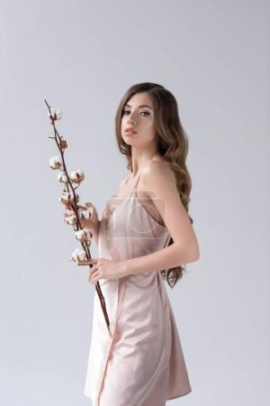 sensual girl posing with cotton flowers, isolated on grey