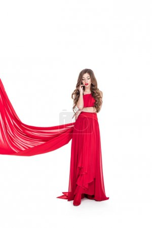 beautiful woman posing in red dress with veil, isolated on white