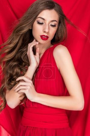 attractive curly girl posing in glamorous dress with red chiffon on background