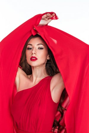 sensual woman posing in red dress with veil, isolated on white