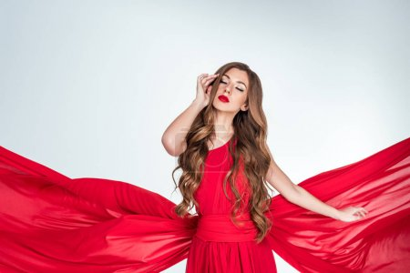 beautiful sensual woman posing in red clothes, isolated on grey