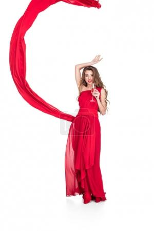 Photo for Glamorous girl in red with chiffon veil holding champagne glass, isolated on white - Royalty Free Image